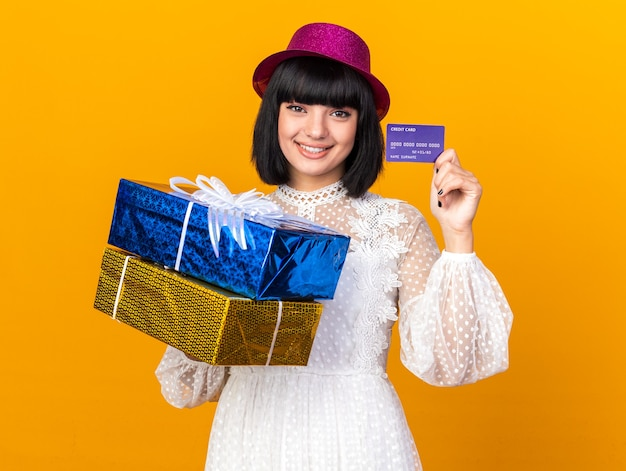 Smiling young party girl wearing party hat holding gift packages and credit card looking at front isolated on orange wall