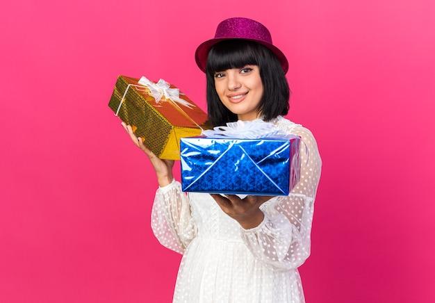 Sorridente giovane ragazza che indossa un cappello da festa che tiene in mano pacchetti regalo isolati sulla parete rosa con spazio di copia