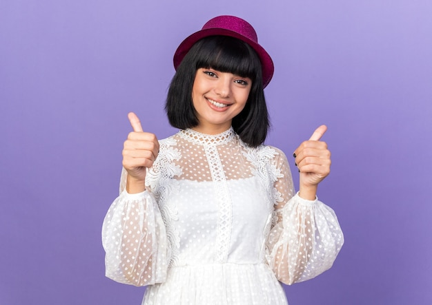 紫色の壁に分離された親指を示すパーティー帽子をかぶって笑顔の若いパーティーの女の子