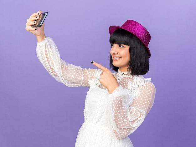 보라색 벽에 격리된 전화를 가리키는 셀카를 찍는 프로필 보기에 서 있는 파티 모자를 쓰고 웃고 있는 젊은 파티 소녀