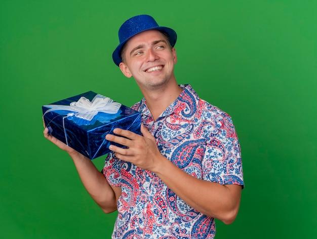 Ragazzo sorridente del partito giovane che guarda al lato che porta il contenitore di regalo blu della tenuta del cappello isolato su fondo verde