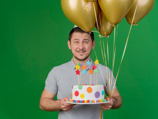 Ragazzo sorridente del partito giovane che indossa il cappello di compleanno che tiene torta con palloncini isolati su verde