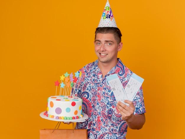 オレンジ色に分離されたケーキとチケットとギフトを保持している誕生日の帽子をかぶって笑顔の若いパーティー男