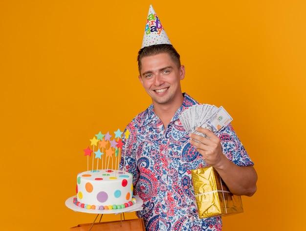 オレンジ色に分離されたケーキと現金で贈り物を保持している誕生日の帽子をかぶって笑顔の若いパーティー男