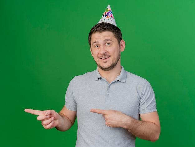 緑で隔離の側で誕生日のキャップポイントを身に着けている若いパーティーの男を笑顔