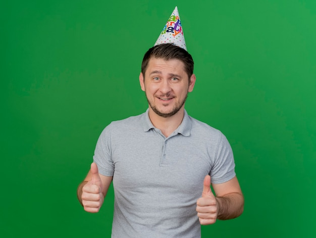 緑で隔離の親指を示す誕生日の帽子をかぶって笑顔の若いパーティーの男