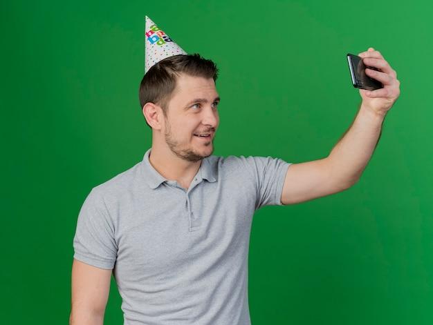 誕生日の帽子をかぶって笑顔の若いパーティーの男は、緑に分離された自撮り