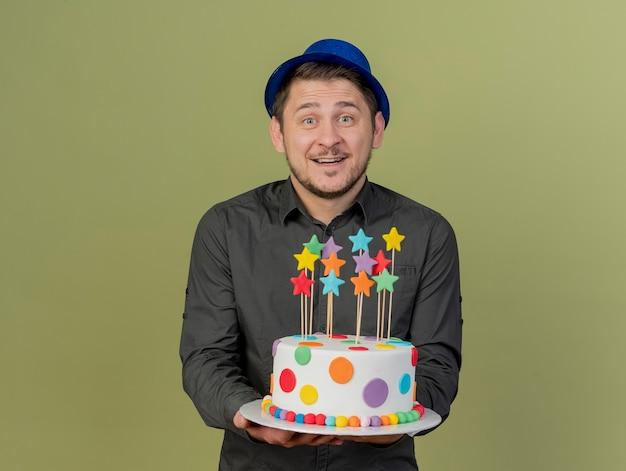 검은 셔츠와 올리브 그린에 고립 된 케이크를 들고 파란색 모자를 쓰고 웃는 젊은 파티 남자