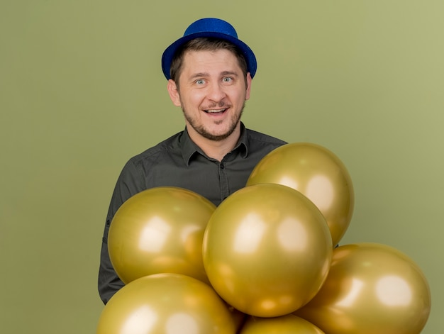 올리브 그린에 고립 된 풍선 뒤에 검은 셔츠와 파란색 모자 서 입고 젊은 파티 남자 미소