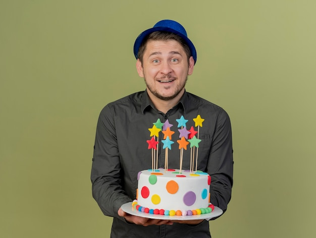 Ragazzo sorridente del partito giovane che indossa la camicia nera e torta blu della tenuta del cappello isolata su verde oliva