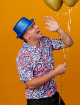 Улыбающийся молодой тусовщик в синей шляпе держит воздушные шары и зовет кого-то изолированного на оранжевом