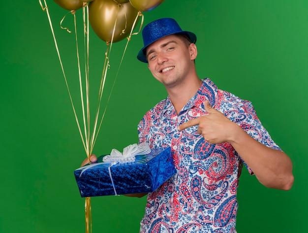 風船を保持し、緑に分離されたギフトボックスを保持し、ポイントする青い帽子をかぶって笑顔の若いパーティー男