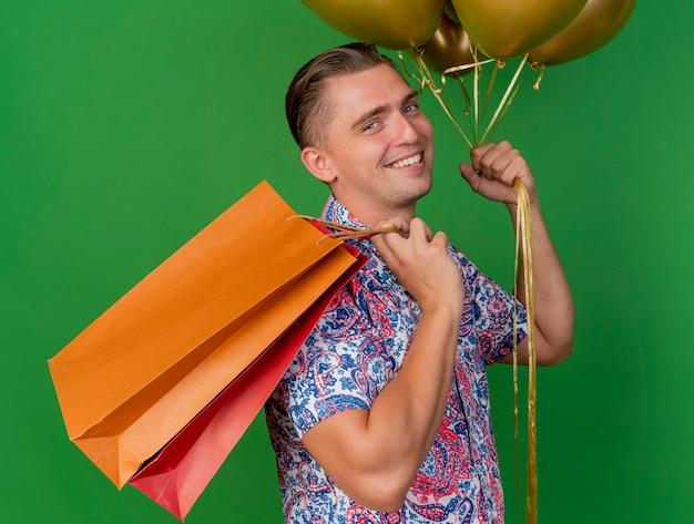 녹색에 고립 된 어깨에 선물 가방을 넣어 풍선을 들고 파란색 모자를 쓰고 웃는 젊은 파티 남자