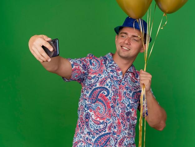 Ragazzo sorridente del partito giovane che indossa il cappello blu che tiene palloncini e prendere un selfie isolato sul verde