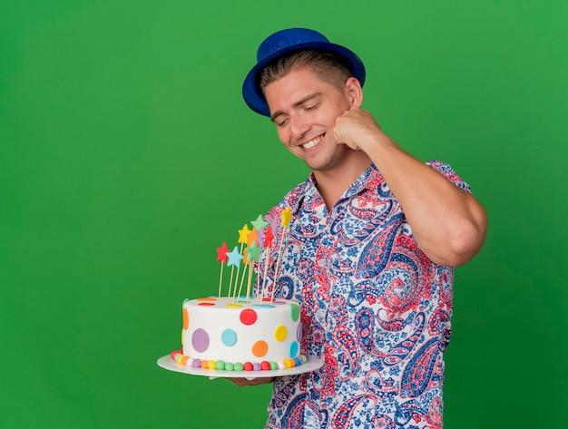 Ragazzo sorridente del partito giovane che indossa il cappello blu che tiene e che esamina la torta che mette la mano sulla guancia isolata sul verde