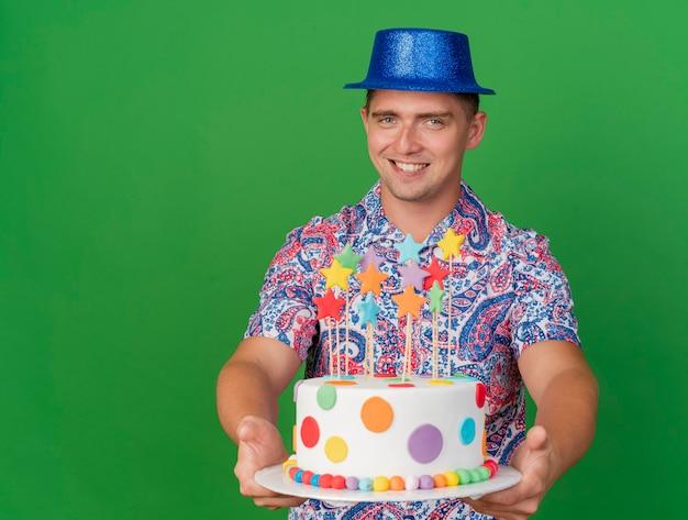 Ragazzo sorridente del partito giovane che porta il cappello blu che tiene fuori la torta isolata sul verde