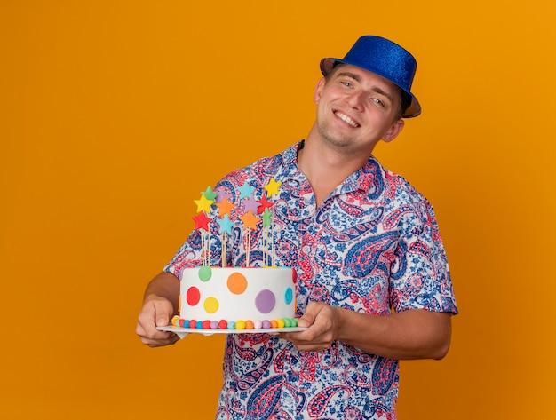 Ragazzo giovane sorridente del partito che porta il cappello blu che tiene fuori la torta isolata sull'arancia