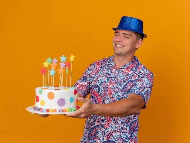 Ragazzo giovane sorridente del partito che porta il cappello blu che tiene fuori la torta al lato isolato sull'arancio Foto Gratuite