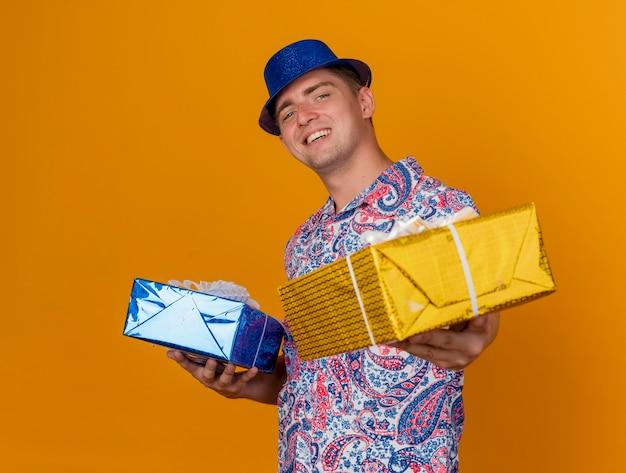 Ragazzo giovane sorridente del partito che porta il cappello blu che tiene fuori i contenitori di regalo isolati sull'arancio