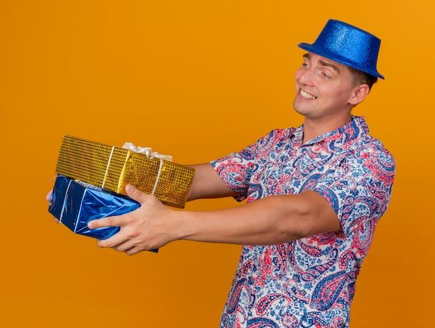 Ragazzo giovane sorridente del partito che porta il cappello blu che tiene fuori i contenitori di regalo al lato isolato sull'arancio Foto Gratuite