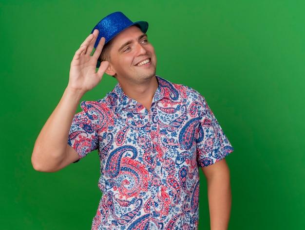 緑に分離されたこんにちはジェスチャーを示す青い帽子をかぶって笑顔の若いパーティー