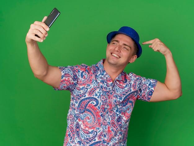 파란색 모자를 쓰고 웃는 젊은 파티 녀석은 셀카를 찍고 녹색 배경에 고립 된 자신을 가리 킵니다.
