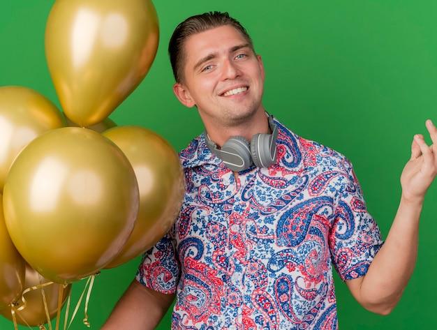 Ragazzo sorridente del partito giovane che indossa la maglietta colorata e le cuffie intorno al collo che tiene i palloncini che diffondono la mano isolata sul verde