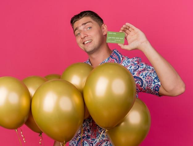 Ragazzo sorridente del partito giovane che indossa la camicia colorata in piedi tra palloncini che tengono la carta di credito isolata sul colore rosa