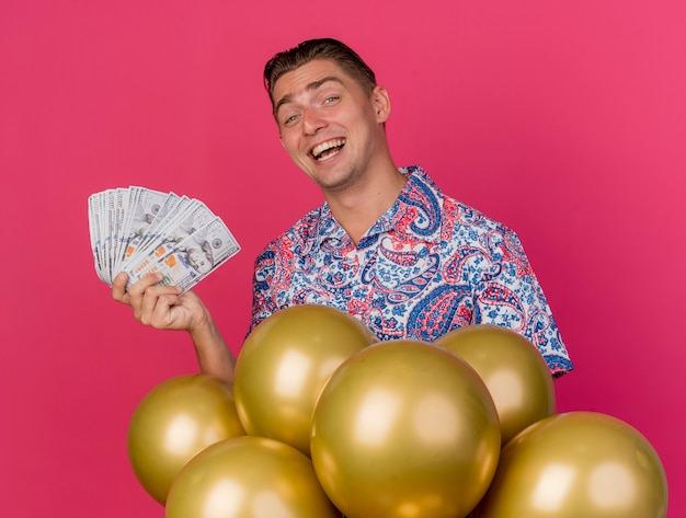 Smiling young party guy wearing colorful shirt standing behind balloons and holding cash isolated on pink