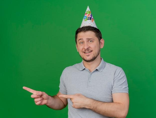 Ragazzo sorridente del partito giovane che indossa una camicia grigia e punte di berretto di compleanno sul lato isolato sul verde