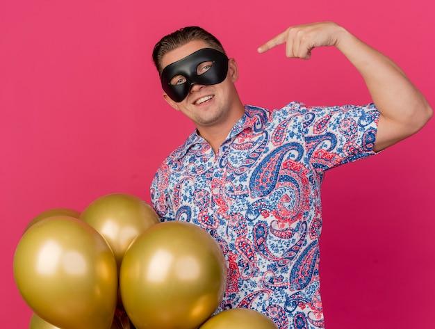 핑크에 고립 된 자신에 풍선과 포인트를 들고 가장 무도회 아이 마스크를 쓰고 웃는 젊은 파티 남자