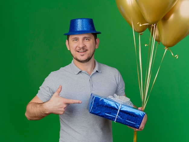 Smiling young party guy wearing party hat holding and points at gift box with balloons isolated on green