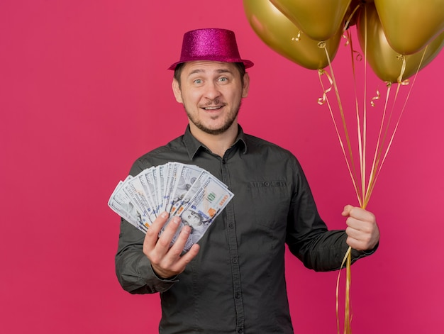 Smiling young party guy wearing pink hat holding balloons with cash isolated on pink