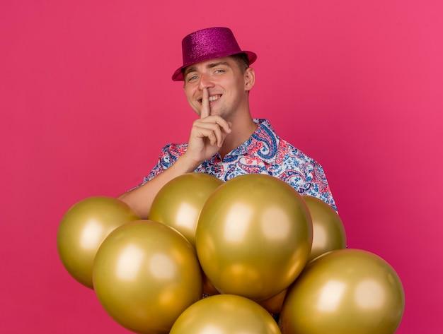 風船の後ろに立っているピンクの帽子をかぶって、ピンクで隔離の沈黙のジェスチャーを示す笑顔の若いパーティーの男