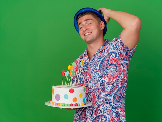 Smiling young party guy with closed eyes wearing blue hat holding cake putting hand behind head isolated on green background