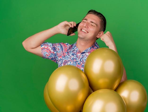 Ragazzo sorridente del partito giovane con gli occhi chiusi che indossa la camicia colorata in piedi dietro i palloncini e parla al telefono mostrando il gesto di sì isolato sul verde