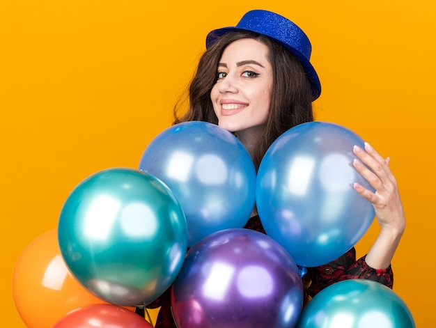 Smiling young party woman wearing party hat standing behind balloons touching one looking at front isolated on orange wall