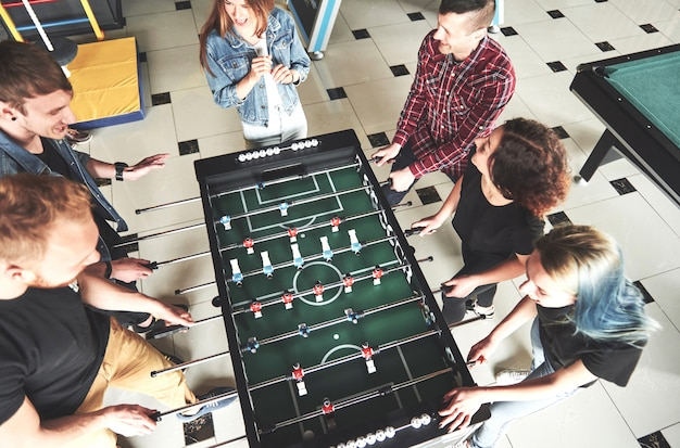 Smiling young people playing table football while indoors