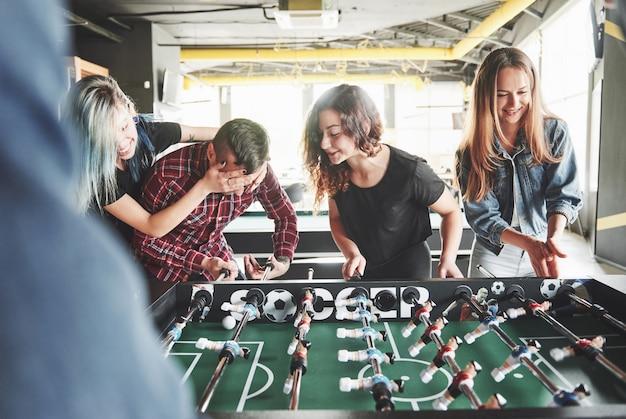 실내에서 테이블 축구를하는 젊은 사람들이 웃고