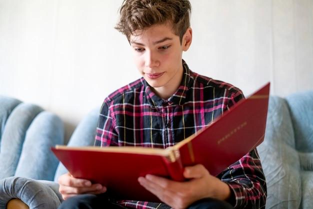Улыбающийся молодой человек, наблюдая семейный фотоальбом дома на диване у