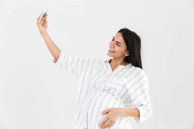 白い壁の上に孤立して立っている若い妊娠中の実業家の笑顔、selfieを取る