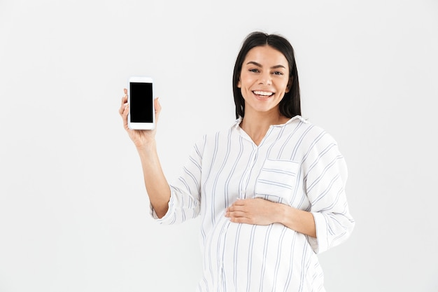 Smiling young pregnant businesswoman standing isolated over white wall, showing blank mobile phone