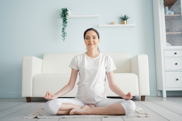 Smiling young pregnant lady in white meditates amd looks at camera sitting in yoga position on floor at home closeup