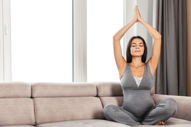 自宅で若い妊婦の笑顔、ソファに座って、ヨガの練習をしています