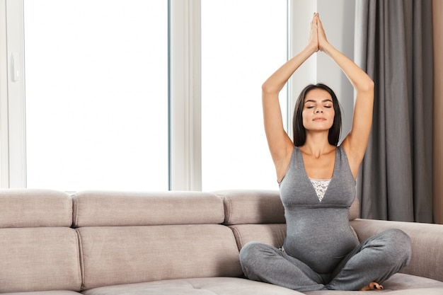 Smiling young pregnant woman at home, sitting on a couch, doing yoga exercises