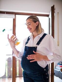 Улыбается молодая беременная женщина, стоя и глядя на банку сока.