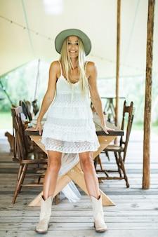 カウボーイハットとブーツ、白いドレスを着て、屋外の木製のテーブルにもたれて若いきれいでセクシーな金髪の女性の笑顔