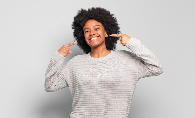 Smiling young pretty black woman pointing at herself
