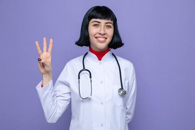Smiling young pretty caucasian girl in doctor uniform with stethoscope gesturing three with fingers