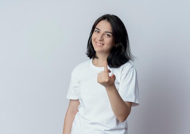 Улыбающаяся молодая симпатичная кавказская девушка делает жест на камеру на белом фоне с копией пространства
